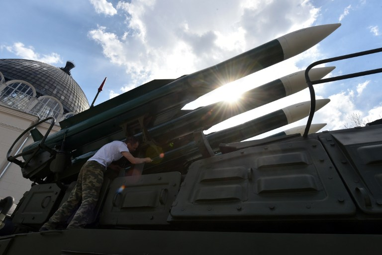 An employee paints a BUK air defence missile system at an open-air military exhibition in Moscow on April 29, 2015. Russia will celebrate the 70th anniversary of the 1945 victory over Nazi Germany on May 9. AFP PHOTO / VLADIMIR NOVIKOV